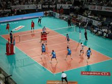 An image from an international match between Italy and Russia in 2005. A Russian player on the left has just served, with three men of his team next to the net moving to their assigned block positions from the starting ones. Two others, in the back-row positions, are preparing for defense. Italy, on the right, has three men in a line, each preparing to pass if the ball will reach him. The setter is waiting for their pass while the middle hitter with no. 10 will jump for a quick hit if the pass will be good enough. Alessandro Fei (number 14) has no passing duties and is preparing for a back-row hit on the right side of the field. Note the two liberos with different color dress. Middle hitters/blockers are commonly substituted by liberos in their back-row positions.