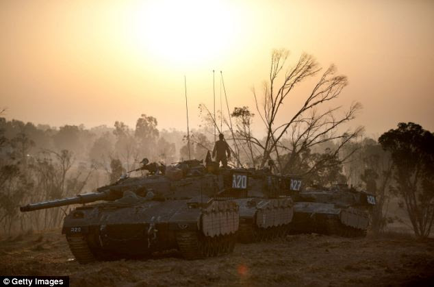 Israeli soldiers prepare weapons and vehicles in a deployment area as the conflict between Palestine and Gaza enters its seventh day
