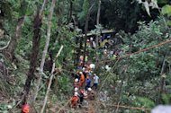 Malaysian emergency services personnel work to rescue passengers after a bus carrying tourists and local residents fell into a ravine near the Genting Highlands, about an hour's drive from Kuala Lumpur on August 21, 2013. At least 37 people are confirmed dead
