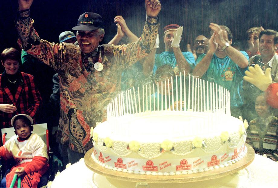 Mandela, em frente a um bolo com muitas velas e varias criancas com deficiencia e alguns adultos em volta, comemorando.