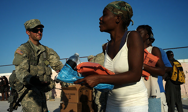 Un marine reparte víveres y agua entre las víctimas del terremoto de 'Cité Soleil', suburbio de Puerto Príncipe. | AFP
