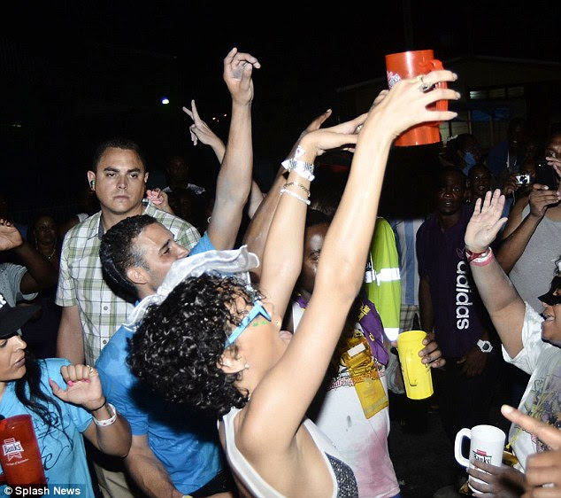 Party time: Rihanna threw her hands up in the air as she partied the night away with the locals