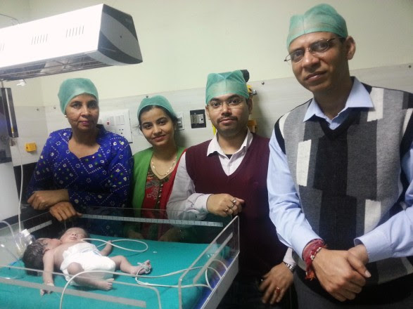 Image: Hospital staff stand next to the girl born with two heads