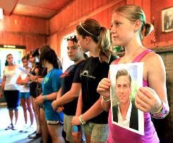 Sarah Henry holds a picture of George Clooney during her cabin's presentation on free thinkers after lunch at Camp Quest in Clarksville, Ohio.