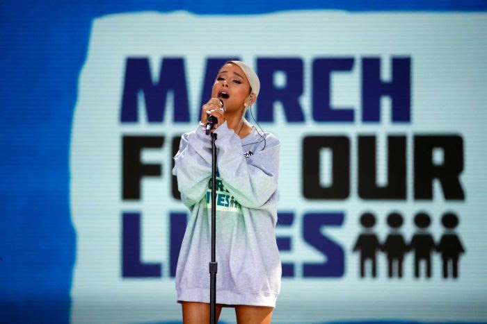 Ariana Grande is seen singing in front of a 'March For Our Lives' banner.