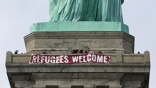 'Refugees Welcome' banner hung on Statue of Liberty in New York - BBC News