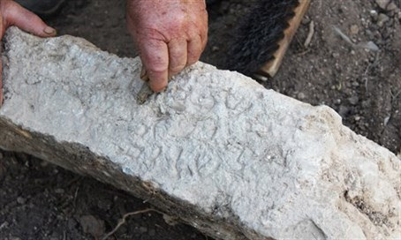 Cleaning one of the Aramaic inscriptions.