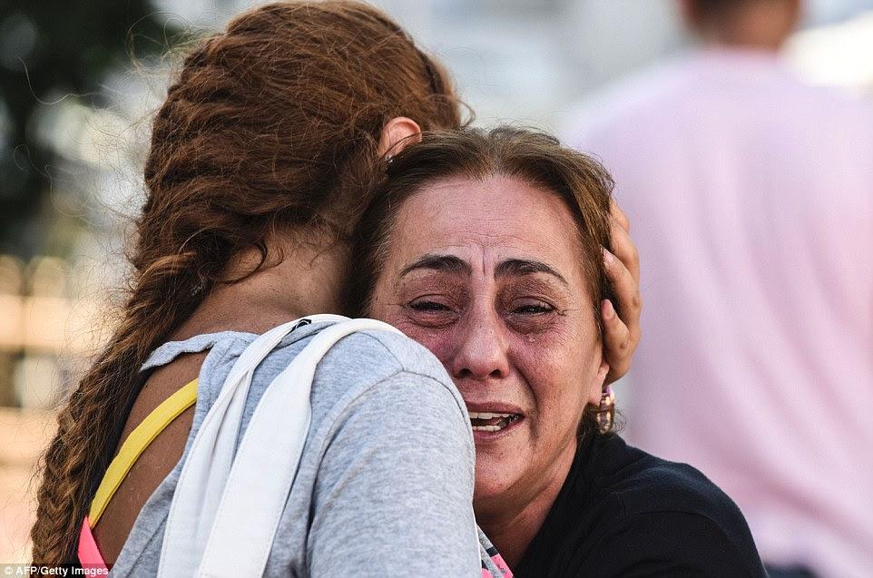 Outra mãe de uma das vítimas é consolado depois de saber o destino de um de seus filhos depois de homens-bomba abriram fogo antes de fundir-se acima
