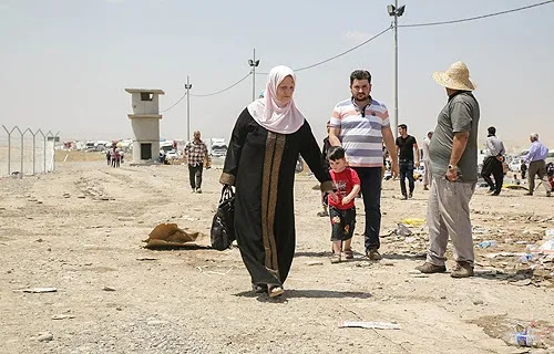 A family at the Khazair checkpoint after fleeing from Mosul, Iraq on June 11, 2014. Credit: R. Nuri UNHCR-ACNUR via Flickr (CC BY-NC-SA 2.0).