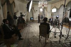 Ο πρόεδρος του Ιράν, στο βάθος δεξιά, κατά τη διάρκεια της συνέντευξής του στην κρατική τηλεόραση.