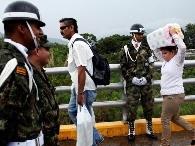 Uma jovem carrega papel higiénico quando ela cruza a fronteira colombiana -venezuelana sobre a ponte internacional Simón Bolívar depois de fazer compras , enquanto um policial colombiano olha. (Foto: REUTERS/Carlos Eduardo Ramirez)