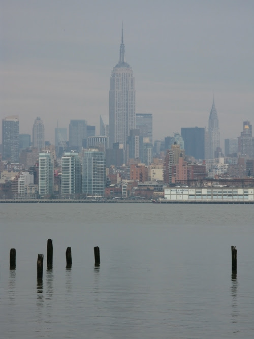 New Jersey pier ruins in the Hudson River with the Empire State Building, NYC