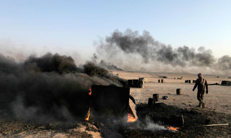 A man walks at a makeshift oil refinery site