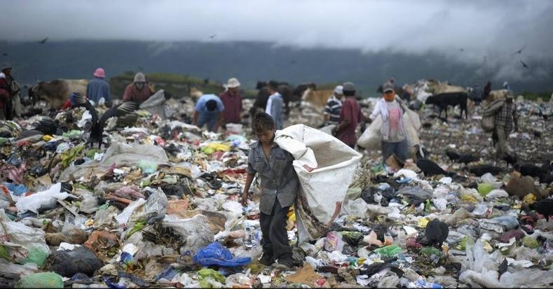 Um menino recolhe resíduos em um aterro sanitário na periferia de Tegucigalpa, Honduras.  De acordo com o Banco Mundial, 64,5 por cento da população de Honduras vive na pobreza, enquanto 42,6 por cento vivem em extrema pobreza (menos de US $ 2,50 por dia).  Em termos de coeficiente de Gini, a desigualdade é avaliado em 53,7.