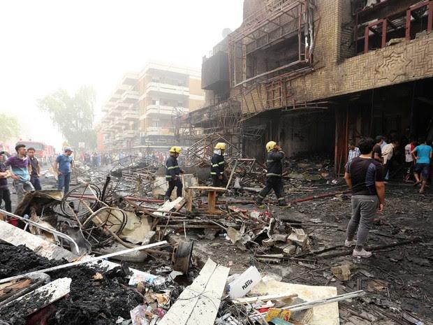 Bombeiros e iraquianos observam destruição deixada após explosão de carro-bomba no centro de Bagdá (Foto: Sabah Arar / AFP Photo)
