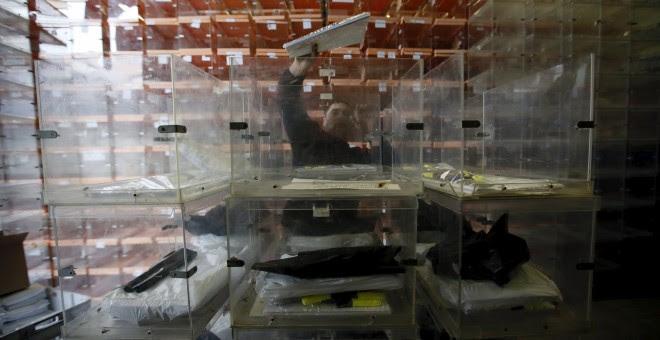 Un operario prepara las urnas para la jornada electoral del 20-D. REUTERS