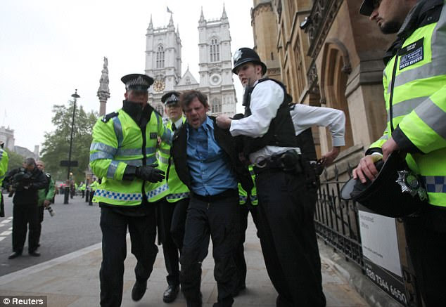Security operation: A man is restrained by police officers outside Westminster Abbey this morning as a huge ring of steel is thrown up around the capital