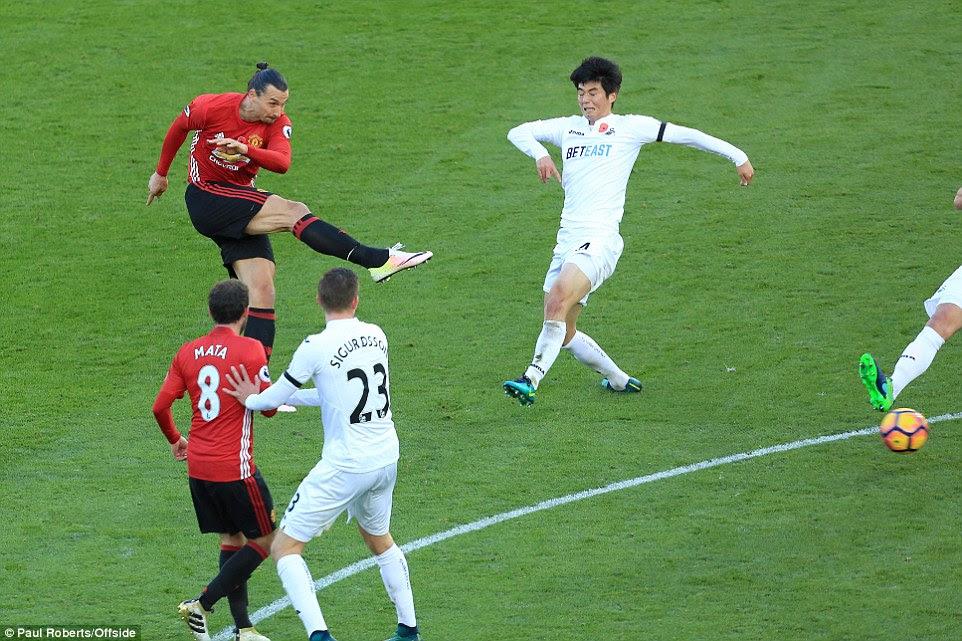 Ibrahimovic dispara a meta para anotar su segundo gol como Swansea centrocampista Ki Sung-Yong no puede cerrar el delantero abajo