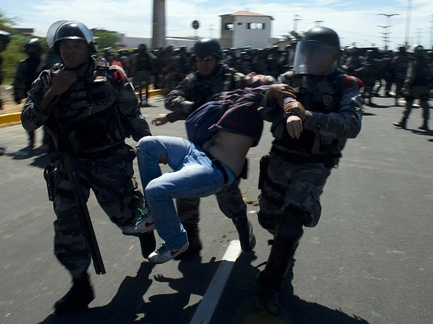 Manifestante ferido é carregado por um policial, em Fortaleza (Foto: Vanderlei Almeida/AFP)