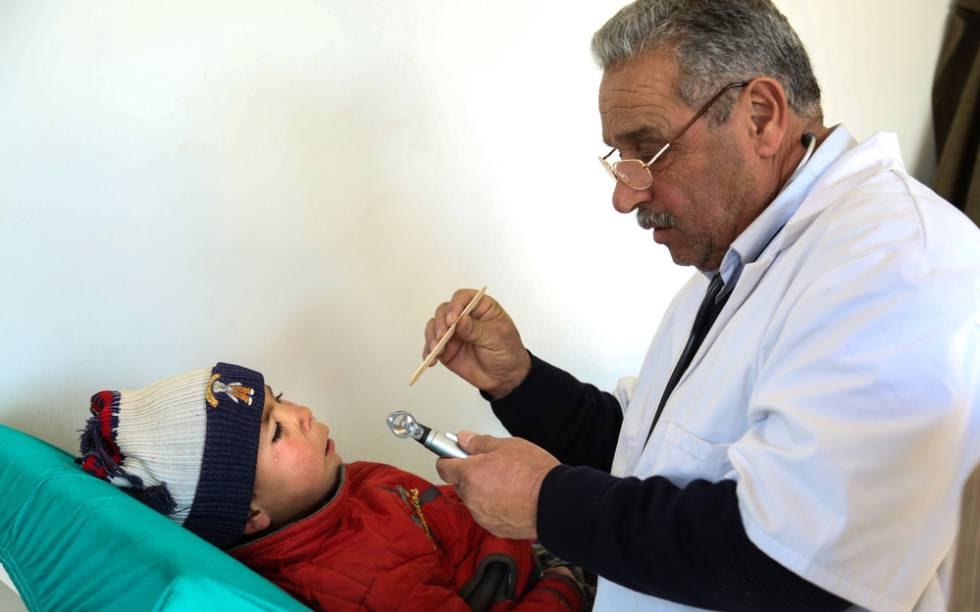 Un doctor de MSF comprueba el estado de salud de un niño recién llegado a uno de los centros de MSF en el norte de Alepo.