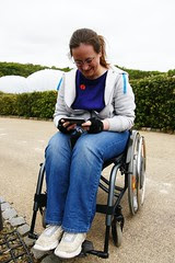 me sitting in my wheelchair, fiddling with my phone, with the Eden biomes in the background
