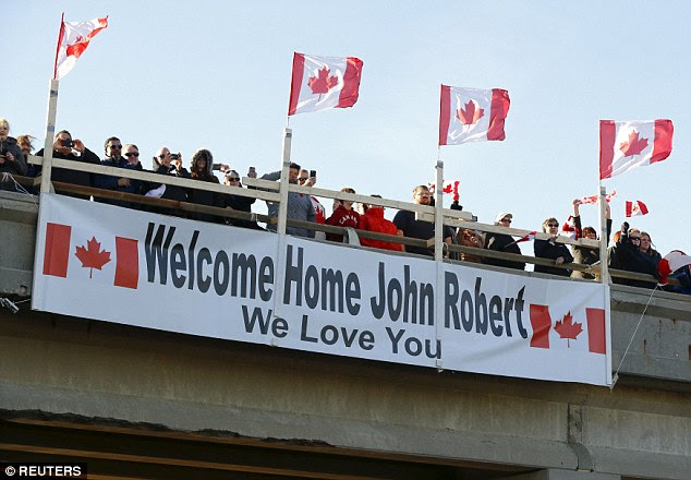 People pay their respects to John Gallagher on an overpass where his hearse passed through in London, Ontario on Friday