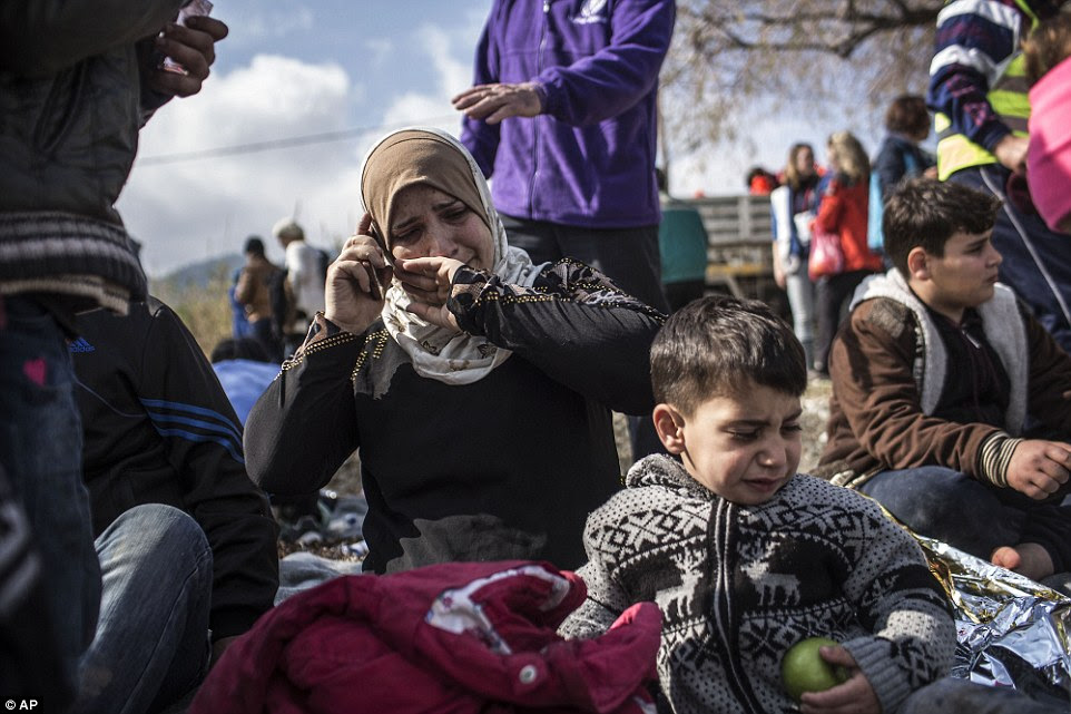 Long road ahead:A Syrian woman cries as she talks to her relatives after her arrival with other refugees and migrants from the Turkish coast to Greece