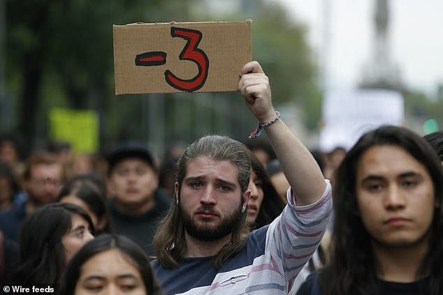 A protester holds up a -3 sign at a protest in Mexico City on April 24. It stands for the three students who were abducted and murdered in March after being mistaken for rival gang members