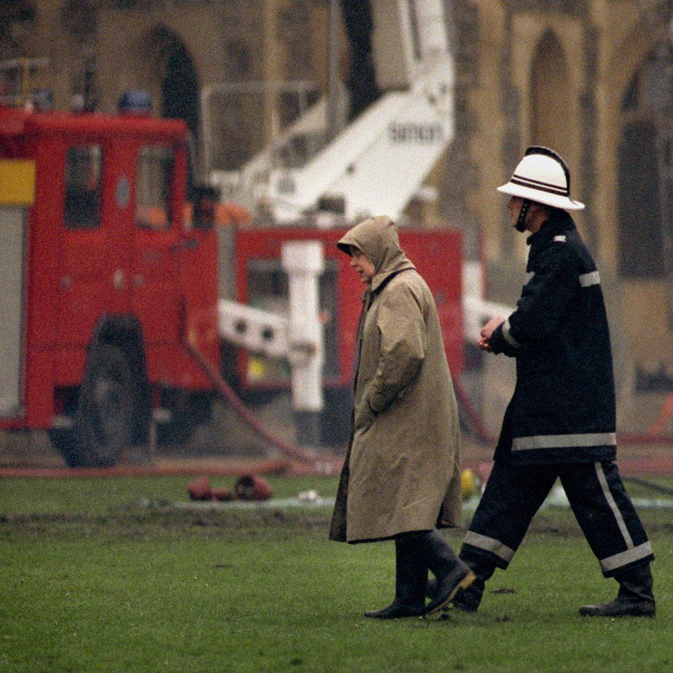 Queen Elizabeth II surveying the scene following the fire at Windsor Castle