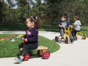 Esmeralda Acosta, left, German Martínez and Tadeo Calderón bike around on the paved tricycle roadway at the daycare center.