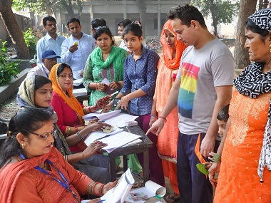 Voters wait to cast their votes at a polling station for the Haryana Assembly elections in Sonepat. PTI