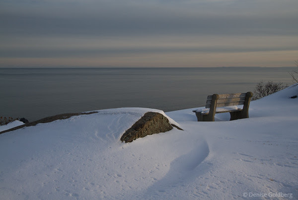 bench buried in snow, looking out to sea