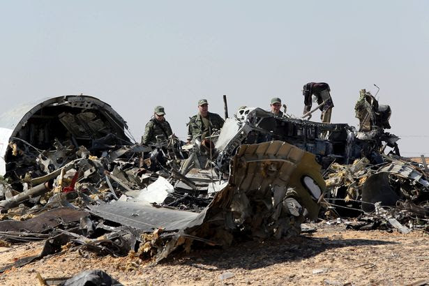 Military investigators from Russia stand near the debris of a Russian airliner
