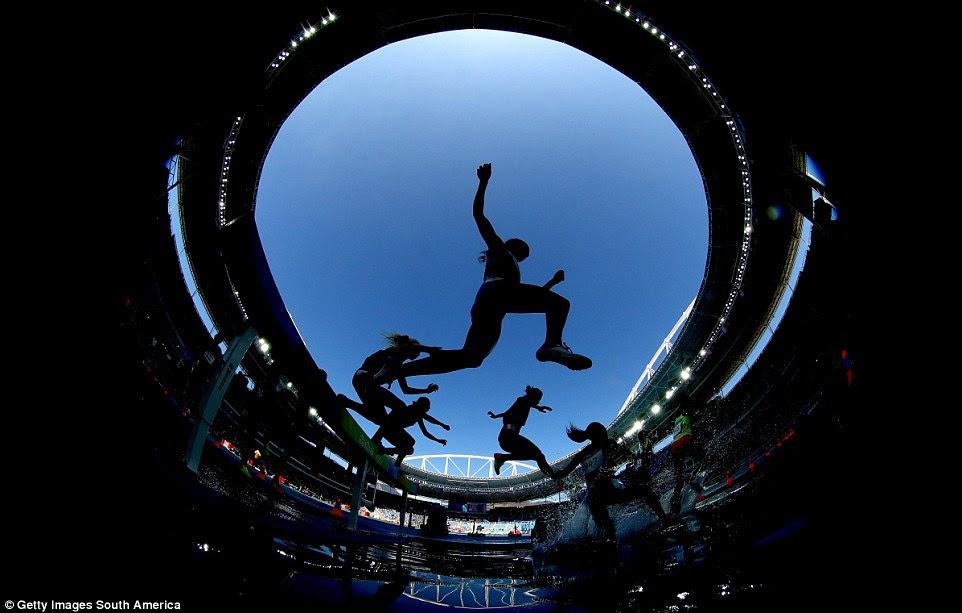 Os atletas salto para a água no steeplechase 3000m das mulheres, que foi evenutally venceu por Ruth Jebet do Bahrein