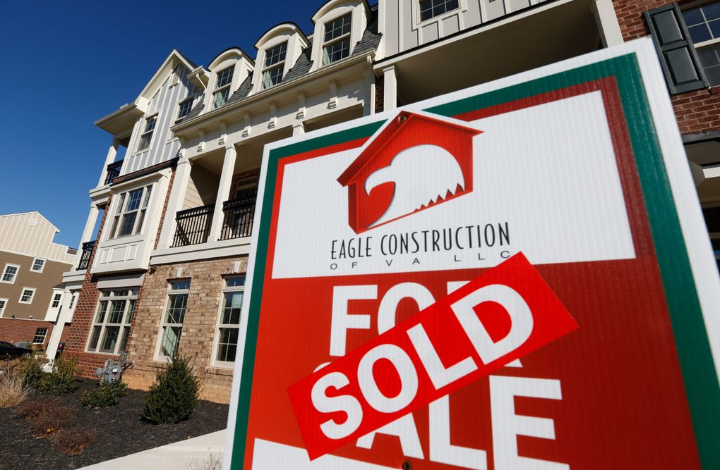 In this Jan. 8, 2015 photo, a sign with a sold sticker is posted in front of a row of new town homes in Richmond, Va. Freddie Mac reports on average U.S. mortgage rates on Thursday, May 21, 2015. (AP Photo/Steve Helber)