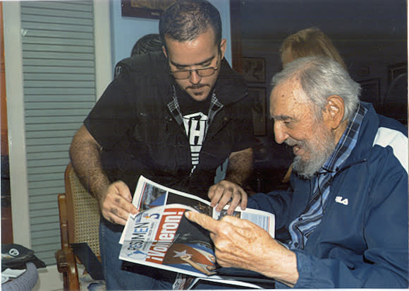Former Cuban President Fidel Castro and President of Cuba's University Students Federation Randy Perdomo look at a newspaper during a meeting in...