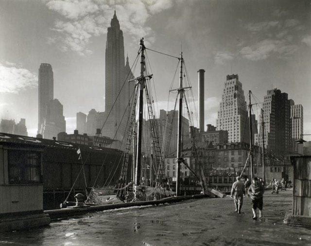 Fulton Street Dock, Manhattan skyline, Manhattan. Men walk on pier where sailing vessels are moored, skyline beyond.