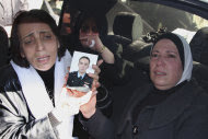 "In this photo taken during a government-organized tour for the media, relatives of William Al-Saleh one of the six elite pilots who the military said were killed in an ambush on Thursday, hold his portrait as they mourn during his funeral procession, in Homs province, Syria, on Saturday Nov. 26, 2011. The military blamed terrorists for the ambush and has vowed to ""cut every evil hand"" that targets the country's security. (AP Photo/Bassem Tellawi)"