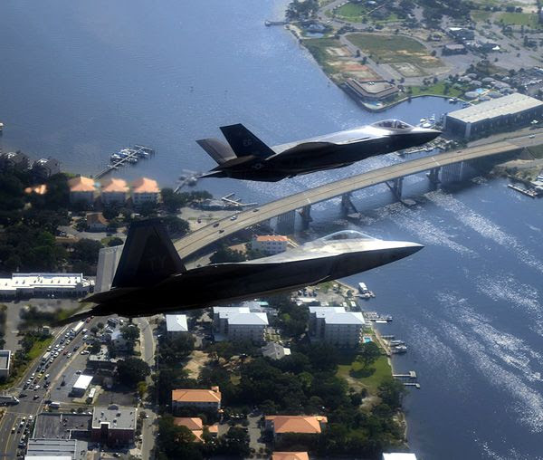 An F-22 Raptor and F-35 Lightning II fly in formation for a training mission.