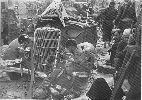Milicianos ante coches destruidos en Toledo en la Guerra Civil. Septiembre de 1936. Fotografía de Hans Namuth/Georg Reisner