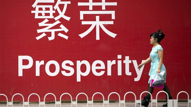 Une femme à Pékin marche devant une pancarte sur laquelle est écrit le mot «Prospérité».