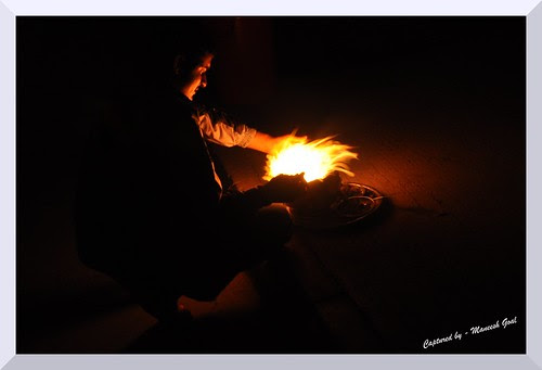 A man trying to protect the holy fire on a windy night during a temple ritual