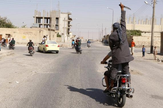 A man holds up a knife as he rides on the back of a motorcycle touring the streets of Tabqa city with others in celebration after Islamic State militants took over Tabqa air base, in nearby Raqqa city August 24, 2014. REUTERS-Stringer