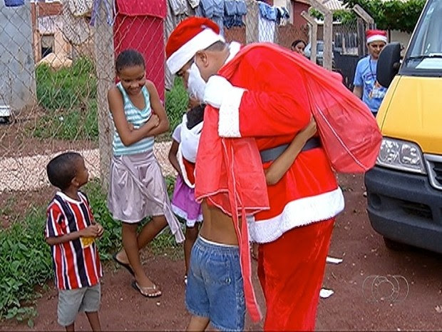 Criança abraça Papai Noel durante entrega de presentes (Foto: Reprodução/TV Anhanguera)