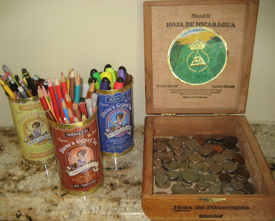 cigar box with coins, and tea tins with pens