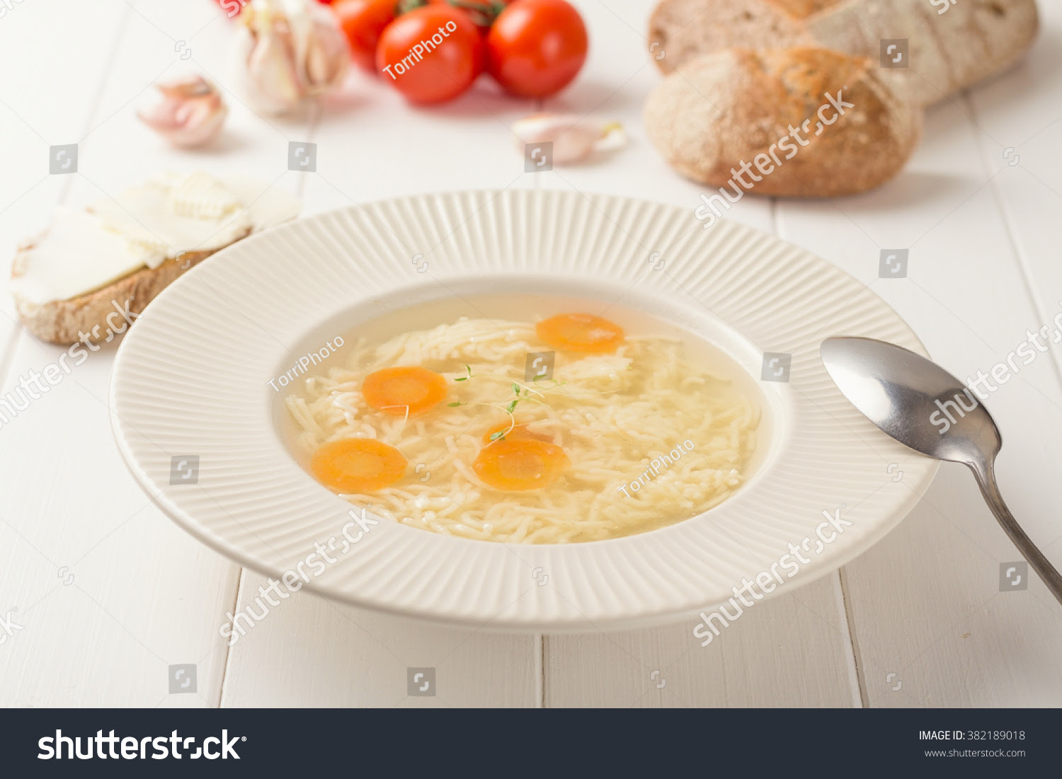 http://www.shutterstock.com/pic-382189018/stock-photo-chicken-broth-with-noodles-and-carrots-in-a-white-plate-on-white-wooden-table-shallow-focus.html