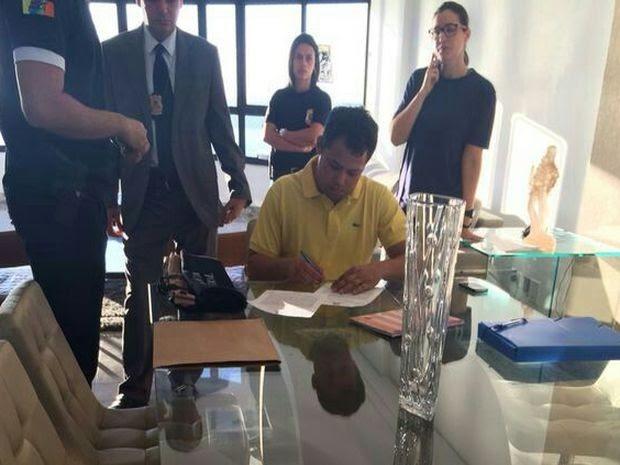 Sukita assina ordem de prisão na casa dele em Aracaju (Foto: Polícia Federal  / Divulgação)