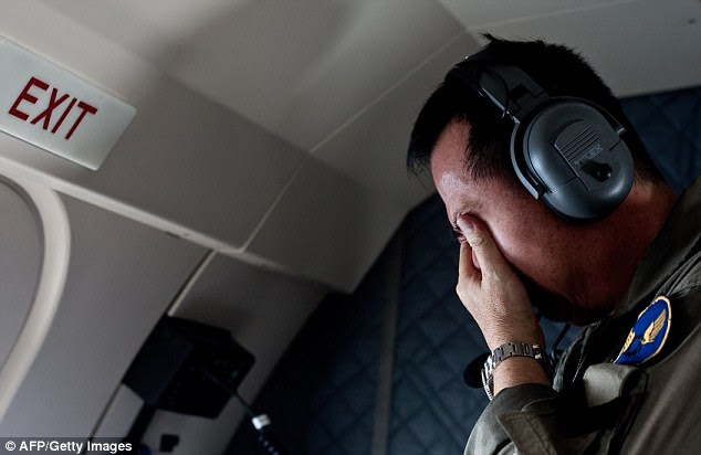 A family member of passengers onboard the missing Malaysian air carrier AirAsia flight QZ8501, reacts after seeing an unidentified floating dead body during a search and rescue (SAR) mission with Indonesian military