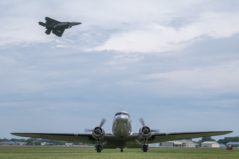 DC-3 taxiing while an F-22 Raptor is landing