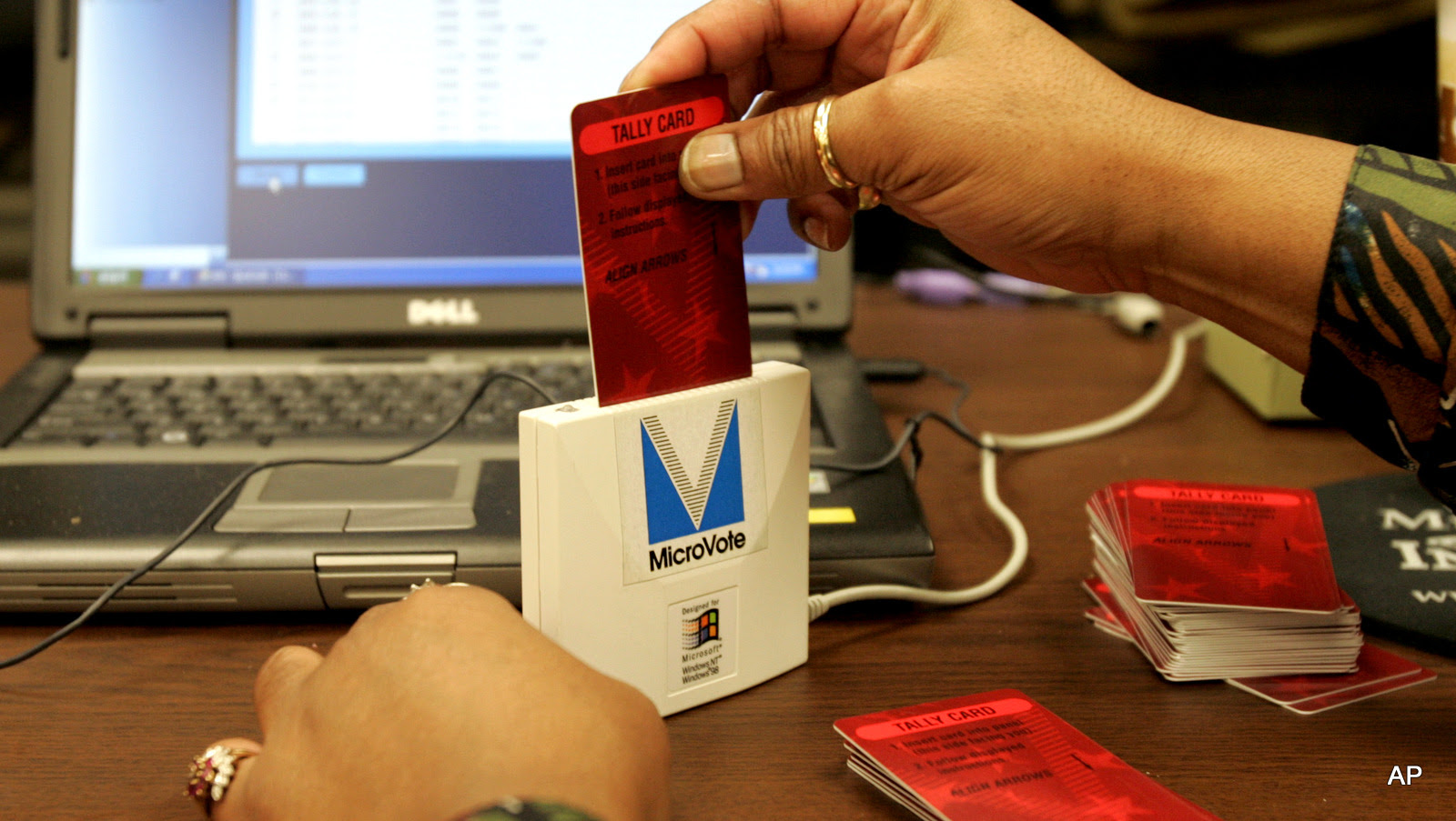 A vote counter inserts a tally card from an electronic voting machine into a card readers as they count votes at the Lake County Government Center in Crown Point, Ind., Nov. 4, 2008.
